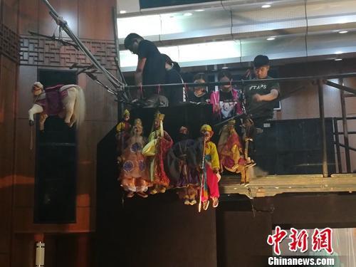 操控木偶的演员们正在做着演出前的准备。上官云 摄