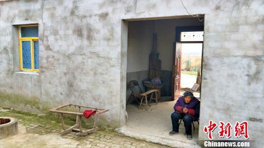 94岁的刘贵英大妈坐在才盖的新房前 夏莹 摄